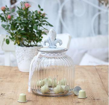 Bild von Glas mit Fleur de lys Betondeckel
